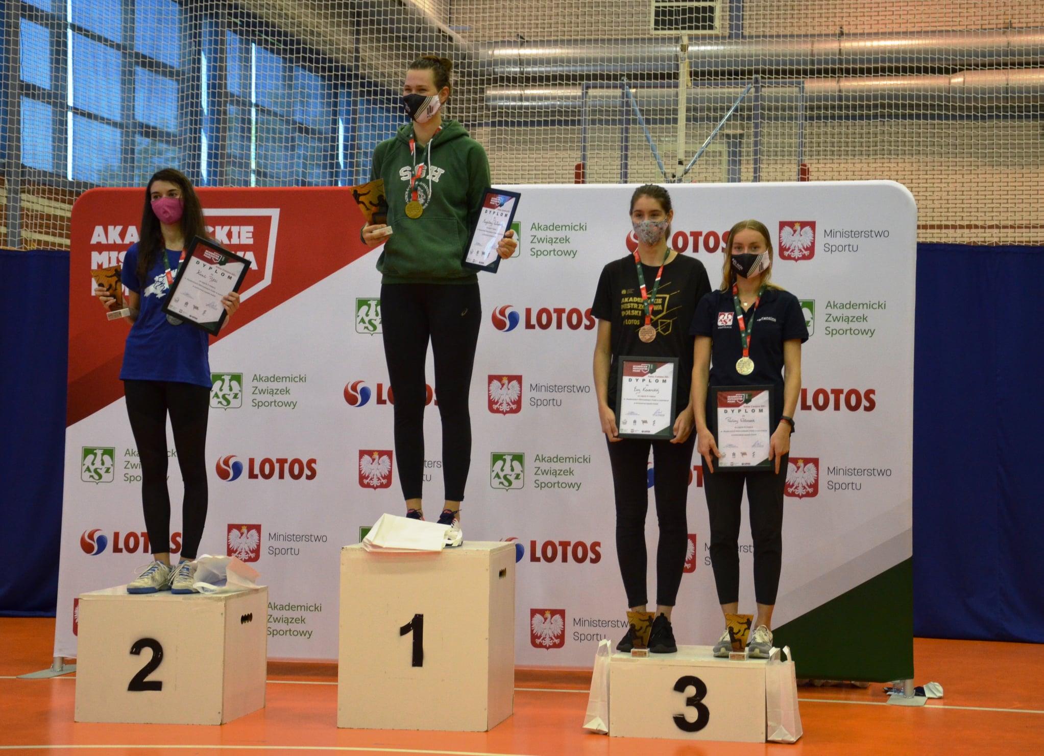 Studentka SGH z medalem i pucharem stoi na podium