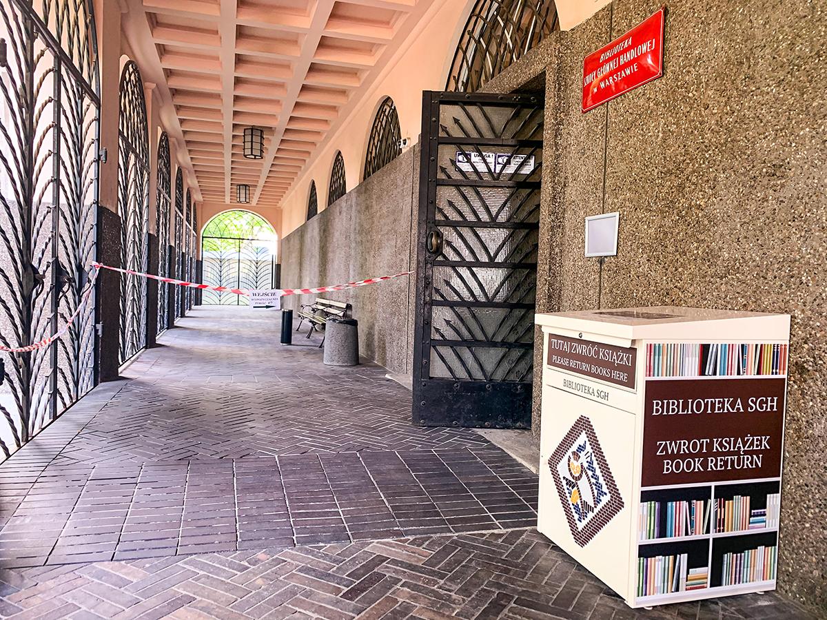 Wrzutnia na książki stojąca przy drzwiach do wejścia głównego Biblioteki SGH.
