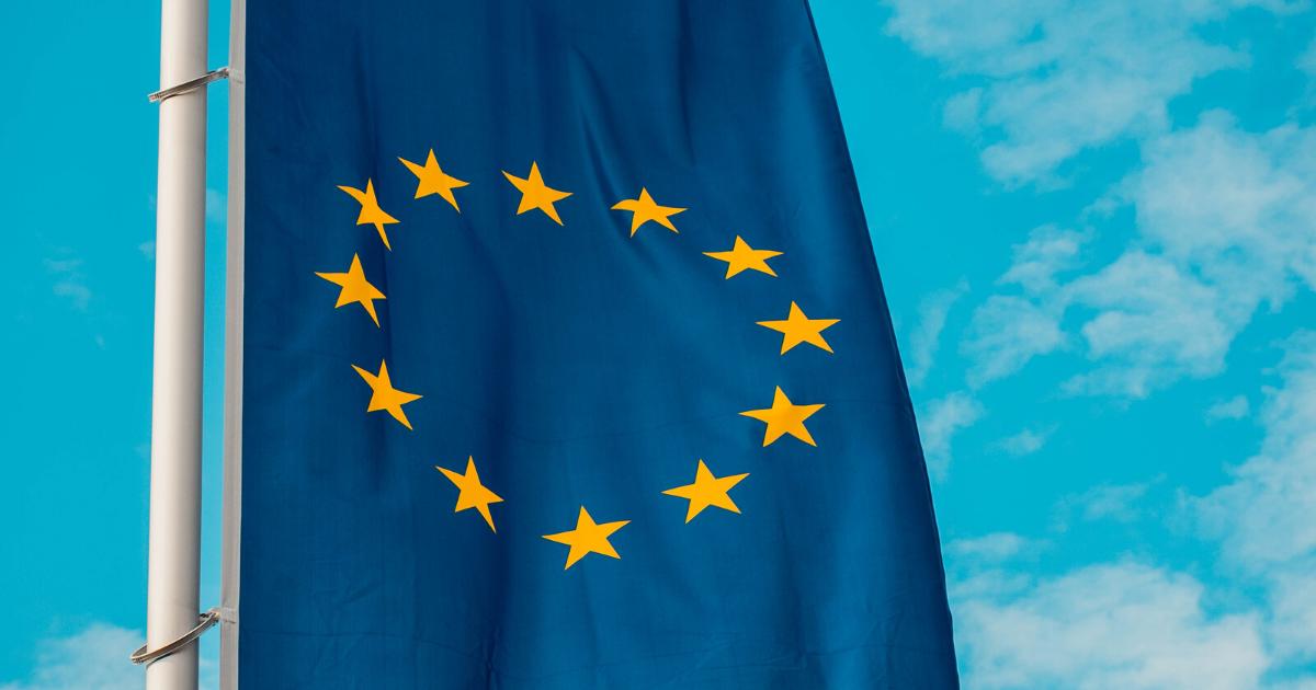 Flaga Unii Europejskiej. Niebieskie tło, na nim 12 żółtych gwiazdek.